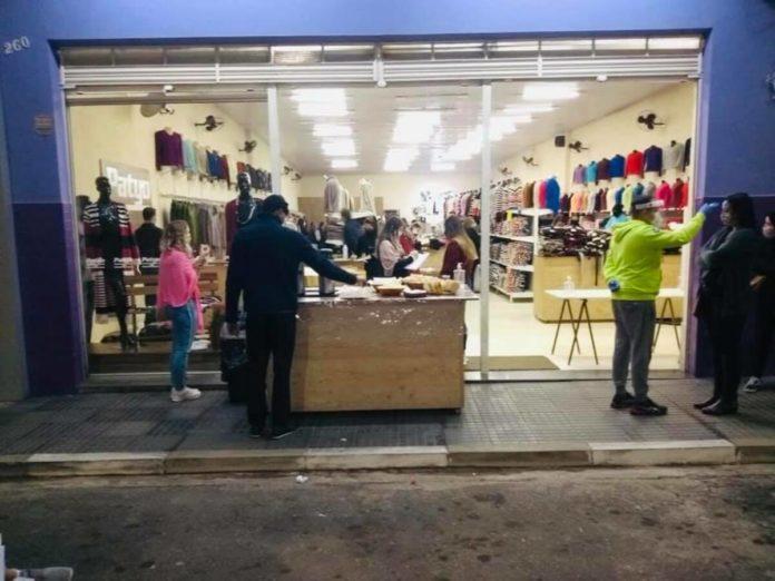 Pessoas passam por uma avaliação antes de entrarem nas lojas